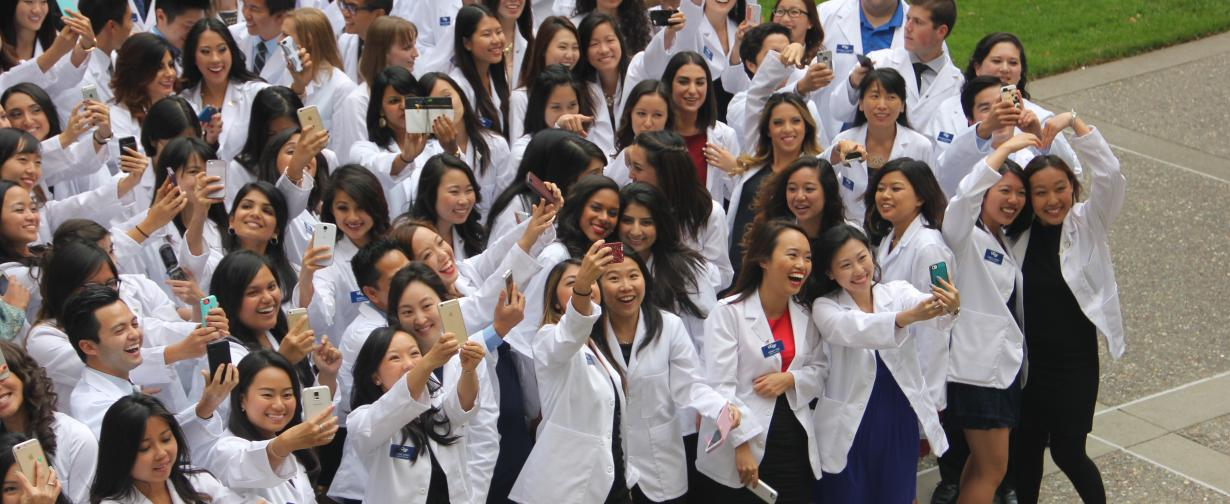 Crowd of PharmD students in white coats, many taking selfie photos