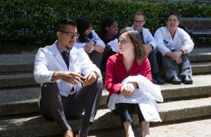 Small group of PharmD students in white coats, sitting on steps
