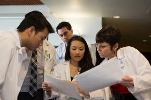 PharmD students look at papers with Marilyn Stebbins, PharmD